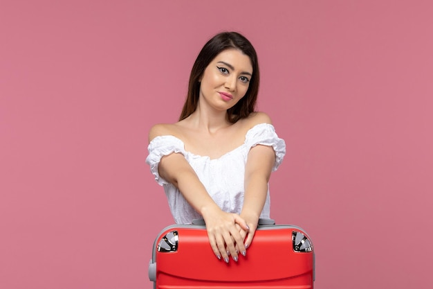Giovane femmina di vista frontale che prepara per la vacanza con la sua grande borsa mentre è felice sul viaggio rosa del fondo che viaggia all'estero viaggio del viaggio del mare