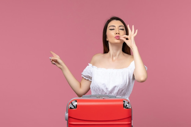 Front view young female preparing for vacation with her red bag on pink desk journey abroad travel sea voyage trip