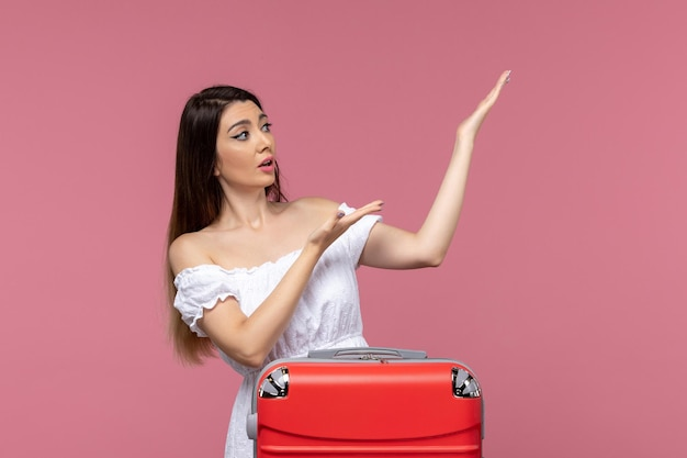 Front view young female preparing for vacation with her red bag on pink desk journey travelling abroad sea voyage trip