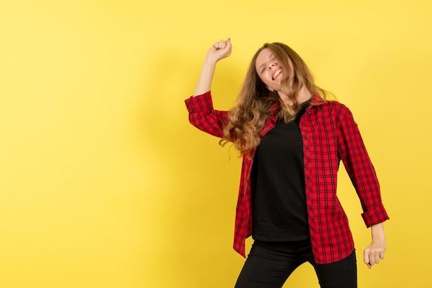 Giovane donna di vista frontale in camicia a scacchi rossa che balla su un'emozione di donna di modello di colore umano sfondo giallo Foto Gratuite