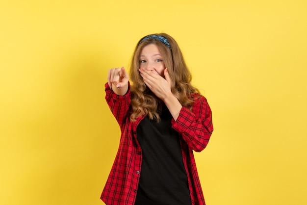 Vista frontale giovane femmina in camicia a scacchi rossa solo in piedi e ridendo su sfondo giallo ragazze modello di colore umano donna