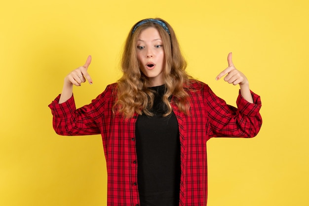 Vista frontale giovane femmina in camicia a scacchi rossa solo in piedi e in posa su sfondo giallo ragazza modello di colore umano donna