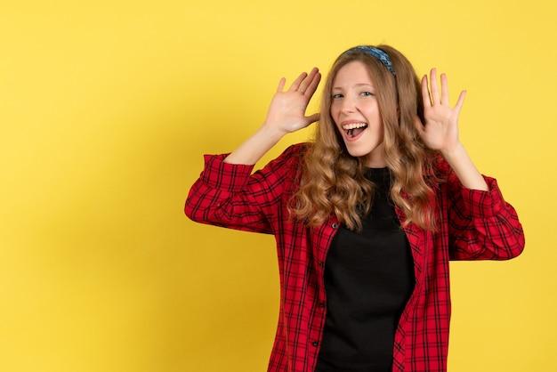 Vista frontale giovane femmina in camicia a scacchi rossa solo in piedi e posa su sfondo giallo ragazze modello di colore umano donna