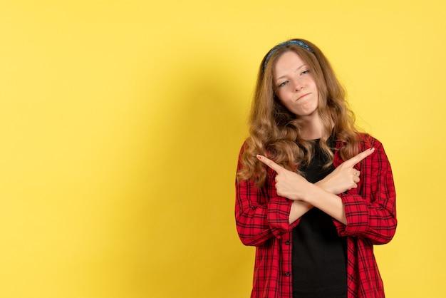 Vista frontale giovane femmina in camicia a scacchi rossa solo in piedi e in posa su sfondo giallo modello ragazza donna umana colore Foto Gratuite