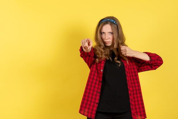 Vista frontale giovane femmina in camicia a scacchi rossa solo in piedi e posa su sfondo giallo modello ragazze donna umana colore emozione
