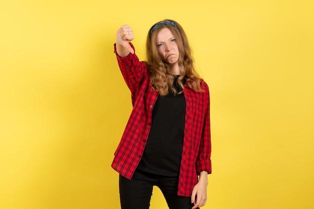 Vista frontale giovane femmina in camicia a scacchi rossa solo in piedi e in posa su sfondo giallo modello ragazze donna colore emozione umana