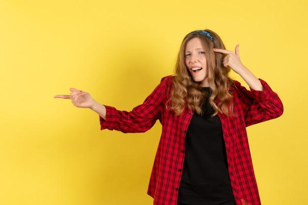 Vista frontale giovane femmina in camicia a scacchi rossa solo in piedi e in posa su sfondo giallo modello ragazze donna colore emozioni umane