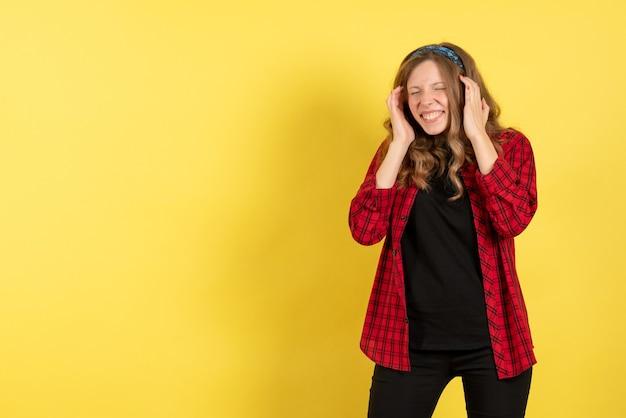 Vista frontale giovane femmina in camicia a scacchi rossa solo in piedi e in posa su giallo scrivania modello ragazze donna colore emozioni umane