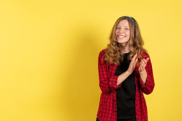 Vista frontale giovane femmina in camicia a scacchi rossa solo in piedi e sorridente su sfondo giallo ragazze modello di colore umano donna