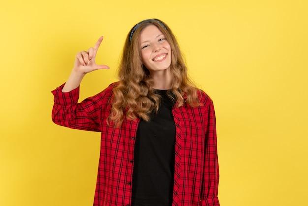 Vista frontale giovane femmina in camicia a scacchi rossa solo in piedi e sorridente su sfondo giallo modello ragazze donna colore emozioni umane