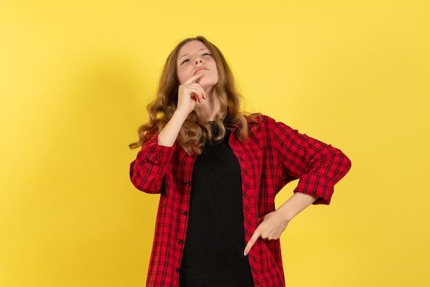 Vista frontale giovane femmina in camicia a scacchi rossa solo in piedi e pensare su sfondo giallo modello ragazze donna umana colore emozioni