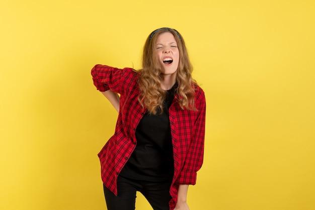 Vista frontale giovane femmina in camicia a scacchi rossa solo in piedi su uno sfondo giallo modello ragazze donna umana colore emozioni