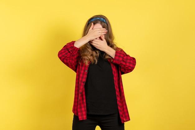 Vista frontale giovane femmina in camicia a scacchi rossa in posa che copre il viso su sfondo giallo modello ragazze donna colore emozioni umano femmina