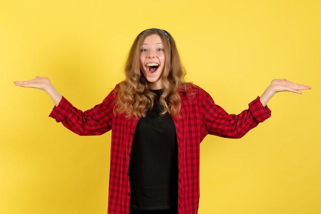 Vista frontale giovane femmina in camicia a scacchi rossa in posa e sentirsi felice su sfondo giallo modello ragazze donna colore emozioni umano femmina