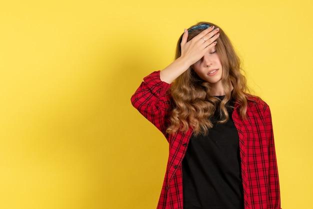 Vista frontale giovane femmina in camicia a scacchi rossa in posa e sensazione di stress su sfondo giallo modello ragazze donna emozione umana femmina colore