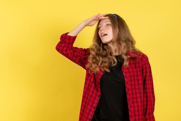 Vista frontale giovane femmina in camicia a scacchi rossa in posa guardando a distanza su sfondo giallo modello ragazze donna colore emozioni umane