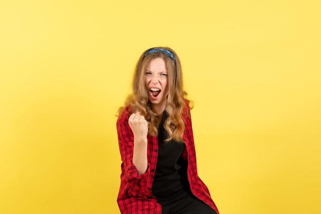 Vista frontale giovane femmina in camicia a scacchi rossa in posa e gioia su sfondo giallo ragazze emozioni colore modello umano donna