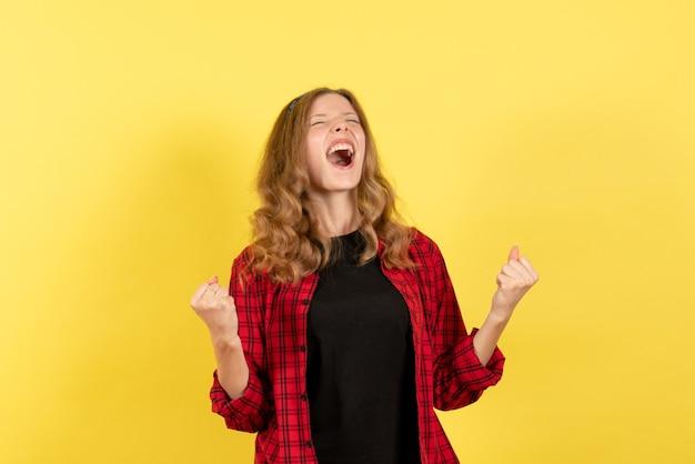 Vista frontale giovane femmina in camicia a scacchi rossa in posa e gioia su sfondo giallo colore umano modello donna emozione