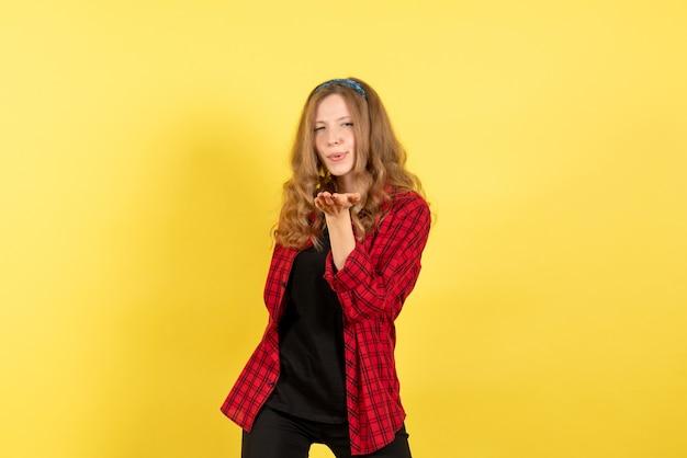 Vista frontale giovane femmina in camicia a scacchi rossa in posa l'invio di baci d'aria su sfondo giallo donna emozione umana modello moda ragazza