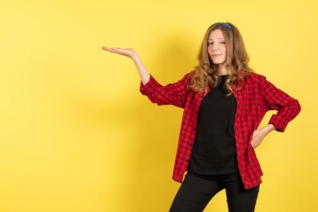 Vista frontale giovane femmina in camicia a scacchi rossa in posa e mostrando le sue emozioni su sfondo giallo colore umano emozione modello moda