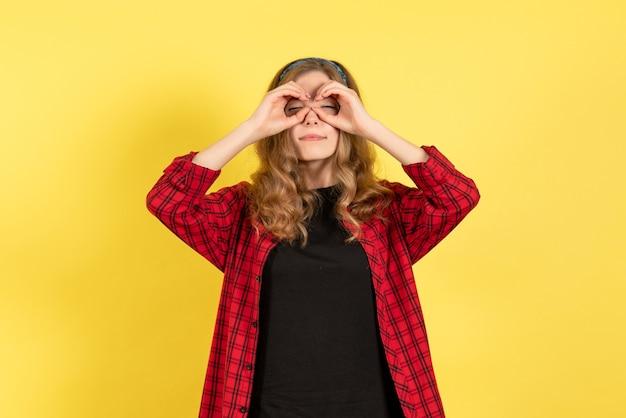 Vista frontale giovane femmina in camicia a scacchi rossa in posa con gli occhi chiusi su sfondo giallo colore umano modello donna emozione