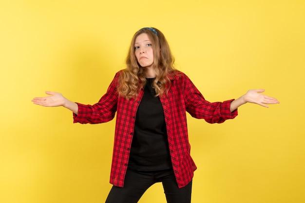 Vista frontale giovane femmina in camicia a scacchi rossa in posa con gesti confusi su sfondo giallo donna emozione umana modello moda ragazza
