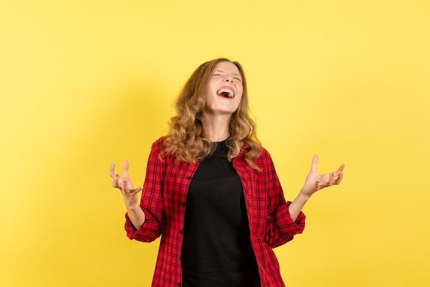 Giovane donna di vista frontale in camicia a scacchi rossa in posa con emozioni su sfondo giallo donna di modello di colore di emozione ragazza umana