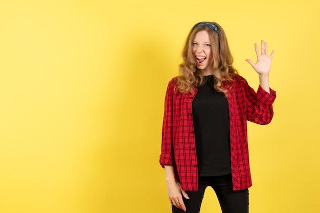 Vista frontale giovane femmina in camicia a scacchi rossa in posa con emozioni su sfondo giallo donna emozione umana modello moda ragazza