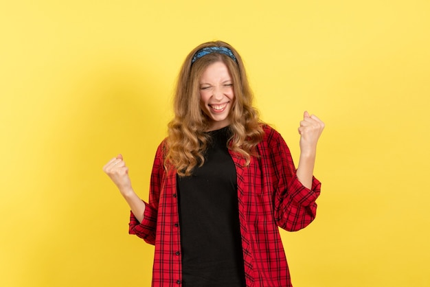 Vista frontale giovane femmina in camicia a scacchi rossa in posa con sentimenti felici su sfondo giallo emozione umana modello di colore donna