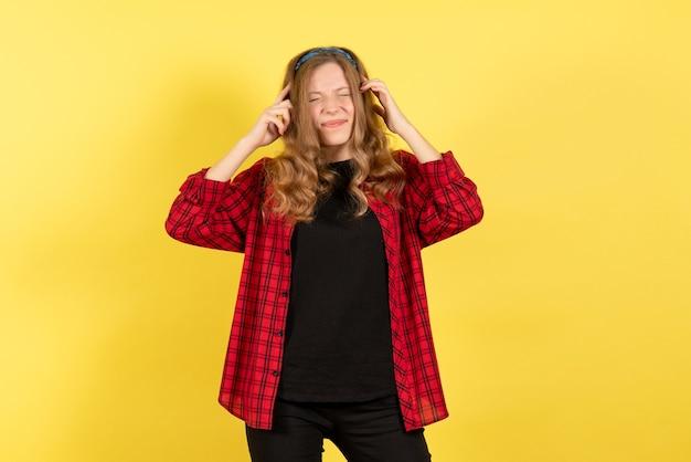 Vista frontale giovane femmina in camicia a scacchi rossa in posa con espressione dolorosa su sfondo giallo emozione umana modello colore donna
