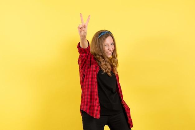Vista frontale giovane femmina in camicia a scacchi rossa in posa con il sorriso su sfondo giallo ragazza umana emozione modello di colore donna