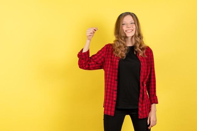 Vista frontale giovane femmina in camicia a scacchi rossa in posa con il sorriso su sfondo giallo emozioni ragazza umana modello di colore donna