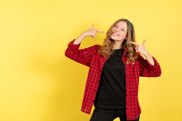 Vista frontale giovane femmina in camicia a scacchi rossa in posa con il sorriso su sfondo giallo ragazze umane emozione modello di colore donna
