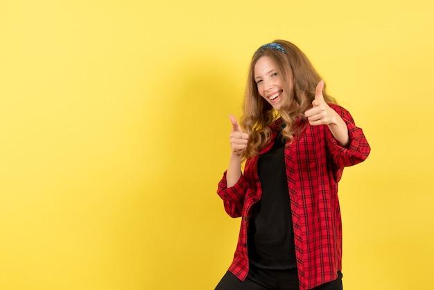 Vista frontale giovane femmina in camicia a scacchi rossa in posa con il sorriso su sfondo giallo donna emozione umana modello moda ragazza