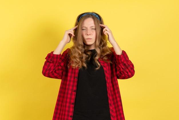 Vista frontale giovane femmina in camicia a scacchi rossa in posa sullo sfondo giallo ragazze donna emozioni modello colore umano