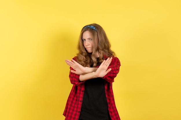 Vista frontale giovane femmina in camicia a scacchi rossa in posa su sfondo giallo modello ragazza donna colore emozione umana