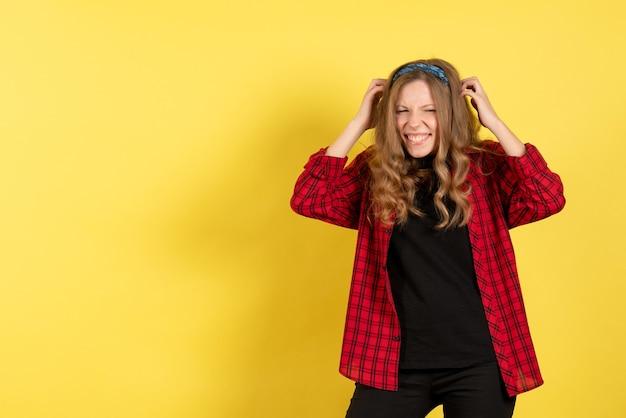 Vista frontale giovane femmina in camicia a scacchi rossa in posa su sfondo giallo modello ragazza donna colore emozioni umano femmina