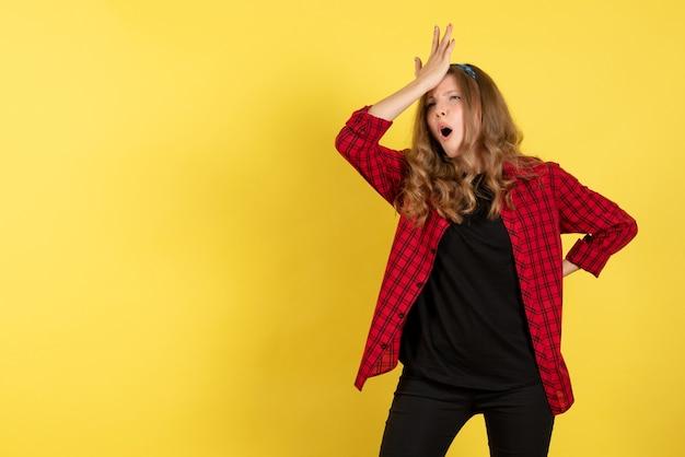 Vista frontale giovane femmina in camicia a scacchi rossa in posa su sfondo giallo modello ragazza donna colore emozioni umane