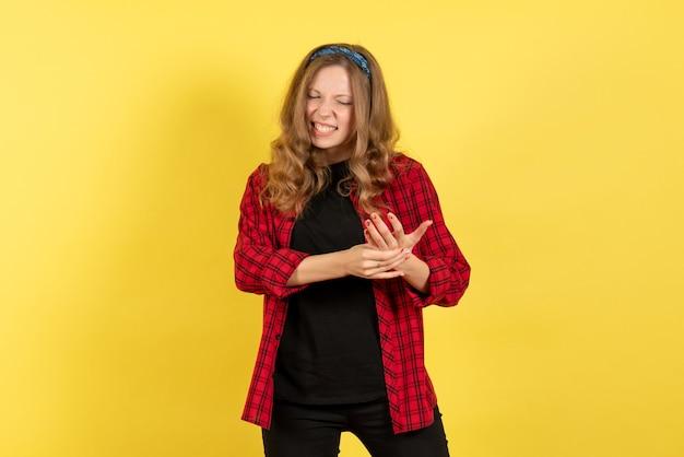 Vista frontale giovane femmina in camicia a scacchi rossa in posa su sfondo giallo modello ragazza donna emozioni umano femmina colore