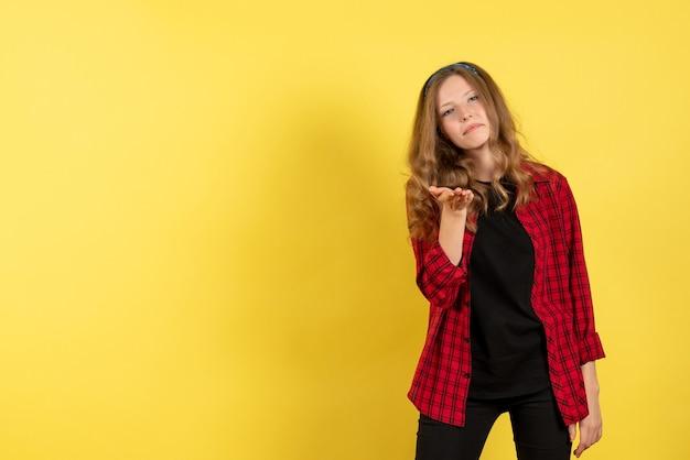Vista frontale giovane femmina in camicia a scacchi rossa in posa su sfondo giallo modello ragazze donna emozioni colore umano femmina