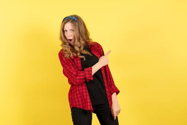 Vista frontale giovane femmina in camicia a scacchi rossa in posa su uno sfondo giallo donna emozione umana modello moda ragazza