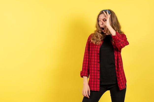 Vista frontale giovane femmina in camicia a scacchi rossa in posa su sfondo giallo donna emozioni umane modello moda ragazza