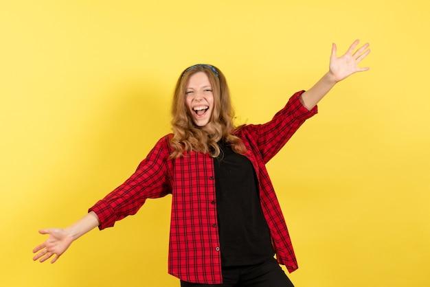 Vista frontale giovane femmina in camicia a scacchi rossa che si rallegra su sfondo giallo donna emozione umana modello moda ragazza