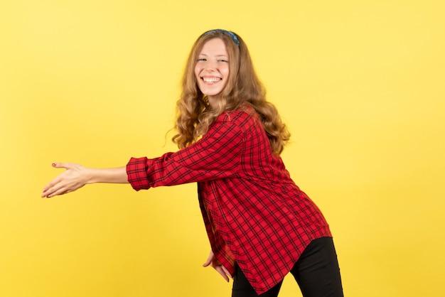 Vista frontale giovane femmina in camicia a scacchi rossa sorridente e saluto qualcuno su sfondo giallo donna emozione umana modello moda ragazza