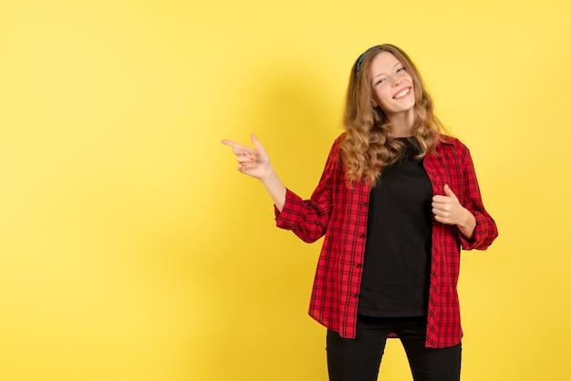 Vista frontale giovane femmina in camicia a scacchi rossa sorridente su sfondo giallo ragazza umana emozione modello di colore donna