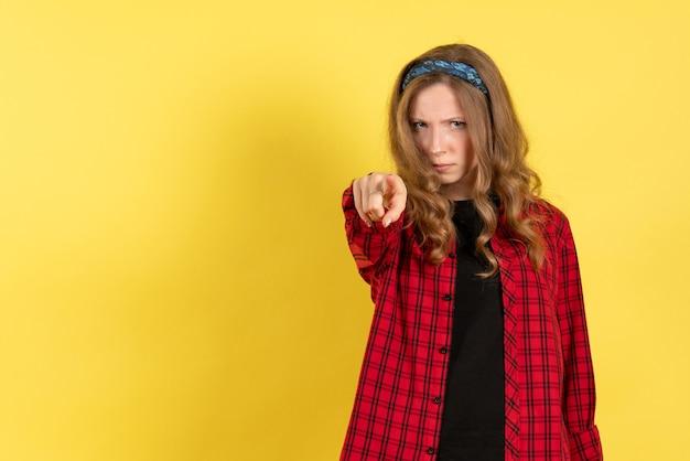 Vista frontale giovane femmina in camicia a scacchi rossa in piedi e che punta su sfondo giallo colore donna modello umano ragazza
