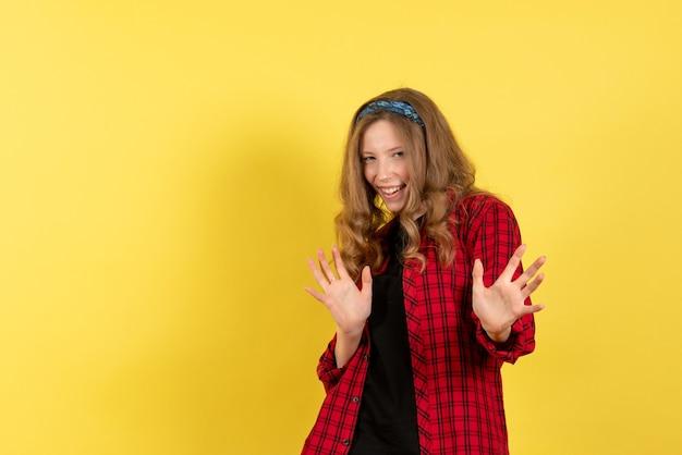 Vista frontale giovane femmina in camicia a scacchi rossa in piedi e in posa su sfondo giallo colore donna modello umano ragazza