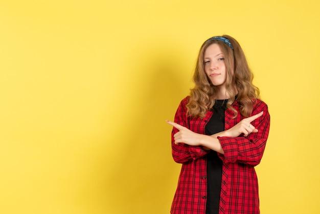 Vista frontale giovane femmina in camicia a scacchi rossa in piedi e in posa su sfondo giallo colori donna modello umano ragazza