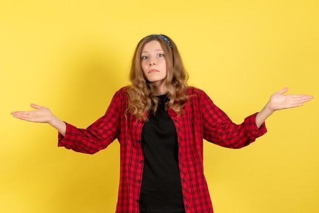 Vista frontale giovane femmina in camicia a scacchi rossa in piedi e in posa su sfondo giallo ragazza modello di colore donna umana