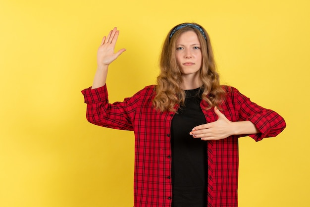 Front view young female in red checkered shirt standing and posing on a yellow background girl color woman model human